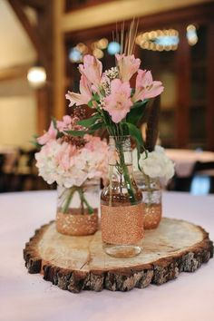 Rustic Tree Stump Centerpieces with Mason Jars and Pink Alstroemeria / http://www.himisspuff.com/rustic-wedding-centerpiece-ideas/18/