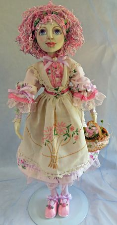 Pretty in Pink.  Another vintage tea towel for her apron.  The buttons on the front of her dress were in an old button box gifted to me by a dear friend-it was her grand-mothers.Her bloomers - which you can't see - were made from embroidered sheer curtains from my parents home.