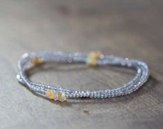 This delicate seed bead and tourmaline piece is so versatile - youll love wearing it as a wrap bracelet, necklace, or anklet. Claspless, made on elastic cord, it is so easy to wear. The tones are neutral enough to go with just about anything, but the design is fresh and lively....  This is a delicate piece with tiny seed beads; tourmaline rondelles measure approx 3mm, and the white jasper measures approx 5mm. Completed piece measures 34 inches, and will typically wrap around the wrist 5…