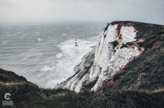 An offshore lighthouse braving stormy waters, captured from the top of white chalk cliffs near Eastbourne in East Sussex, England. Stormy Waters, White Chalk, Beautiful Places In The World, East Sussex, Landscape Photos, Lighthouse, Countryside, Landscapes, Coast