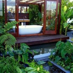 I love how this is an outdoor bath with the option of closing the doors, and the greenery looks beautiful.: