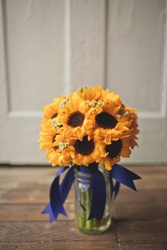 or go simple. bouquet of just sunflowers (( with out the white waxflower)) handtied with blue ribbon. classy, simple. elegant yet country.