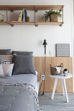 The industrial chic theme extends to the bedroom where again, we see the clever use of copper piping and raw wood being used in a unique above-the-bed storage.