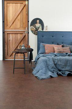 Novilon vtwonen 7444 Raw Denim. Slaapkamer met houten staldeur.