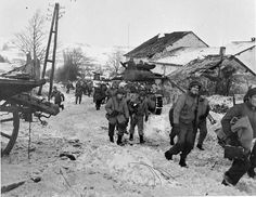 American troops of the Third Army commanded by General George Patton moving through the Belgian town of Bihain.