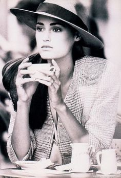 Wearing a classic hat while drinking some tea.