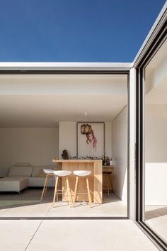 Sliding glass doors connect a Belgian house extension with its poolside patio. (via Gau Paris)
