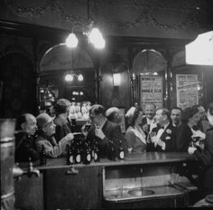 Patrons drinking and chatting at the bar of a music hall, London, England, 1946. Photo by Ralph Morse.