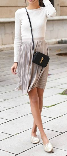 Chic woman on the sidewalk is wearing a metallic pleated skirt and ballerina slippers. Easy does it for simple daytime dressing this spring.