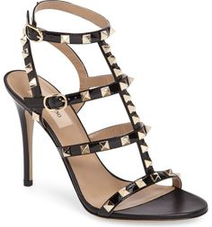Valentino's signature gilded pyramid studs add edgy opulence to this strappy cage sandal shaped from glossy patent leather and lifted by a slim stiletto heel.