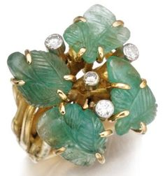Gem-set and diamond ring by Cannilla, Masenza. This ring is made of gold and set with carved emeralds and brilliant-cut diamonds. Accompanied by a matching bangle. Via Diamonds in the Library.