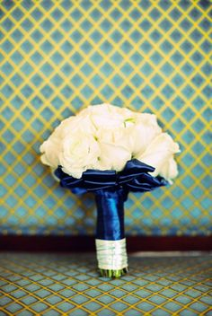 Bridesmaid bouquets of classic cream roses, dressed in navy blue satin (photography by www.desibaytan.com)