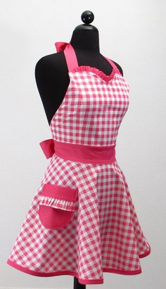 Traditional gingham fabric gives this ruffle kitchen apron a nostalgic air. Destined to become a classic -- and a favorite by all who see it! It features sweetheart neckline, ruffle detailing, and a roomy side pocket with ruffle trim. It is made from 100% cotton -- the high quality stuff -- not the scratchy kind. Adjustable ties at neck and waist. A classic style