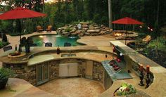 amazing patio setup... pool, kitchen, firepit and waterfall! More at: www.diycozyhome.com