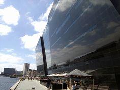 Det Kongelige Bibliotek - Den Sorte Diamant in København K, Region Hovedstaden. Udvidelsen af Det Kongelige Bibliotek er en af Københavns havns helt markante bygningen. På grund af bygningens hældning og de skråt afskårne facader i sort, skinnende marmor, har den fået navnet Den Sorte Diamant. Byggeriet er tegnet af Schmidt, Hammer og Lassen og er fra 1999.