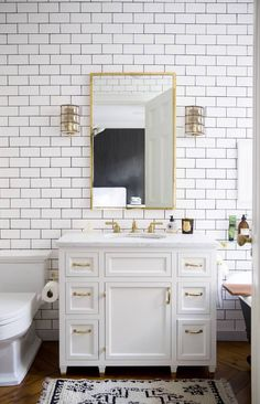 Petite bathroom with floor to ceiling white subway tiles with dark grout, brass hardware and faucet and a vintage black and white Moroccan area rug in front of the sink.