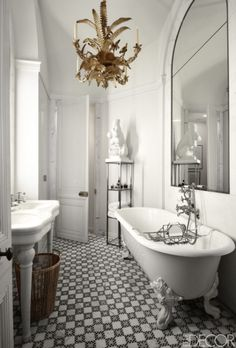 A stunning gold 19th century chandelier hangs above a sparkling white tub in French architect Jacque Grange's Paris bathroom.