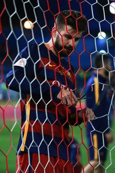 Gerard Pique of FC Barcelona cuts a piece of the goal's net after winning the Copa del Rey Final match between FC Barcelona and Sevilla FC at…