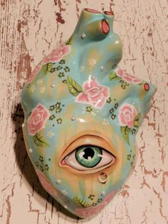 An eye in a flowered greenish pottery heart. i'm done.