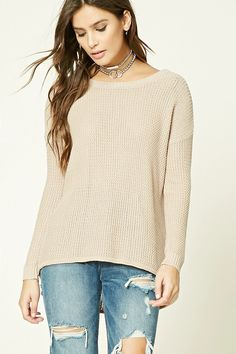 A textured knit sweater featuring a V-cut back, round neckline, curved hem, long sleeves, and a billowy silhouette.