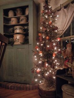 Old Green Cupboard...filled with prim crocks...lighted Christmas tree.