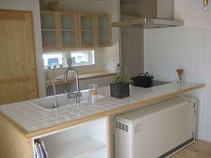 パイン材とホワイトタイルのキッチン。吊戸棚にはチェッカーガラスを使用。