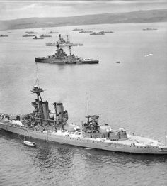 13.5 in battleship HMS Iron Duke, Jellicoe's flagship at Jutland in 1916, seen at Scapa Flow in 1939 when she was in use as a depot / AA ship: her 'B' and 'Y' turrets have been removed. Two 'R' class battleships are in the background: famously, HMS Royal Oak (probably one of those shown) was sunk in the anchorage by U 47 in October that year.