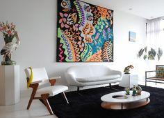 O fundo branco predomina na sala de estar, onde obras multicoloridas pontuam o ambiente com brasilidade. É o caso da tapeçaria do artista Kennedy Bahia, na parede, e da coleção de aves de porcelana das décadas de 1940 e 1960, sobre a mesa de centro da ext (Foto: Marcelo Magnani )