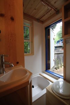 Love this tiny home bathroom- the door/window in front of the tub looks heavenly! Quite a way to relax after a long touring day (if you're somewhere remote, of course)