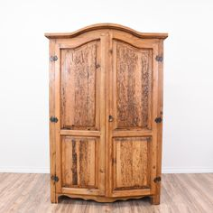 This rustic armoire is featured in a solid wood with a raw pine finish. This large wardrobe is in great condition with cared panels, a curved top and large interior cabinet with shelving. Unique storage piece perfect as a closet!   #rustic #dressers #armoireorwardrobe #sandiegovintage #vintagefurniture