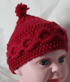 """• """"Failte Babai"""" """"A hundred thousand welcomes Baby!"""" from ©Crazy Celt: Knitting by BJ Doolittle  Tuininga • A baby's first  Celtic  cap with moss stitch to signify a abundance and honeycomb for good luck! • Made from the ultimate in soft handspun  and hand-dyed 100% merino wool • Color: GERANIO • Care: Hand wash in cold water with gentle detergent. Squeeze dry. Shape garment and dry flat."""
