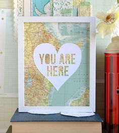 """Whether that certain somebody is close by or far away, this papercut artwork is a sweet reminder to keep close. The words, """"You are here,"""" are carefully cut from textured white cardstock inside of a heart and assembled over a vintage map page. Bodies of water and/or landmasses from the map peek through the cutout, for a layered, one-of-a-kind art piece."""