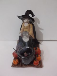 Crone with her crystal ball & hazel wood wand standing before a incense cone burner cauldron in a pumpkin patch