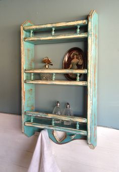Distressed vintage spice rack / wall shelf.  Rustic finish with faded turquoise and white as the accent color.  Features three shelves each with turned spindles, a cut out heart flanked by towel hooks.  $65.  Refinished by New Vintage by Tosh