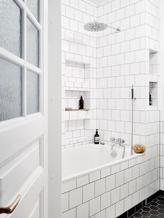 Bathroom with white square subway tile, and a black hexagonal tiled floor
