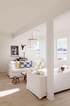 Salón blanco con la luz a través de ventanas.