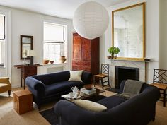 The couches in Michael and Andrew's Gramercy Park home were originally plaid silk taffeta with two seat cushions, so the pair had them reupholstered in navy blue and made single-cushion. And that gilded mirror was originally about three feet taller than it is now, with new glass—Michael and Andrew were having trouble finding the right item for that spot above the mantel, so they had its frame cut down and fit with prettily mottled antique mirror glass to get the look right.