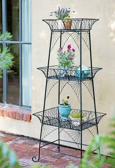 """Wirework Plant Stand. Indoors, this charming tiered plant stand holds potted flowers and houseplants in front of a window or against a wall. Outdoors, you can place a moss liner in the top basket and plant directly in it. The top shelf will hold up to three 9""""-diameter pots. The bottom shelf will hold a 10""""-diameter pot in the middle and two 9""""-diameter pots on the ends. Powder-coated steel wire. Holds up to 75 lbs."""