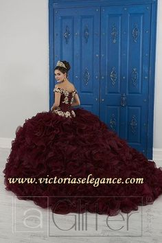 Make a bold statement in his gorgeous off the shoulder ball gown. The bodice is accented with corset boning and beautifully decorated with vibrant beading. Cascades of organza and glitter tulle add volume and a touch of sparkle to finish this look. Quinceanera Dresses Maroon, Mariachi Quinceanera Dress, Mexican Quinceanera Dresses, Mexican Dresses, Quinceanera Party, Tulle Ball Gown, Tulle Balls, Ball Gowns, Types Of Dresses
