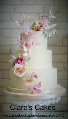 Butterfly Wedding Cake, ivory 3 tier wedding cake with royal iced texture on all tiers. Roses, and butterfly's in dusky pink, peach, pink and ivory for decoration. #beautiful #stunning