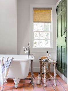 Terra-Cotta Floor Handmade terra-cotta tiles and a claw-foot tub outfit the master bath in this Connecticut cottage. The door conceals a medicine cabinet and linen closet. Terracotta Tiles Bathroom, Beautiful Bathroom Designs, Bathroom Floor Tiles, Bathroom Decor, Terra Cotta Tiles Floors, Beautiful Bathrooms, Tile Bathroom, White Tub, Beautiful Tile Bathroom