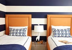 Strong color reigns in this boys room, where twin orange headboards measure up to horizontal stripes. Traditional Home®