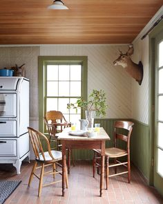 The kitchen's oak table and mismatched chairs are flea-market finds inside a historical farmhouse full of vintage treasures and antiques.