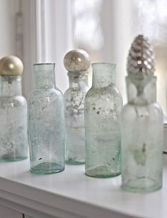 vintage bottles and what looks like to be vintage Christmas Ornament Stoppers. What a grand idea.