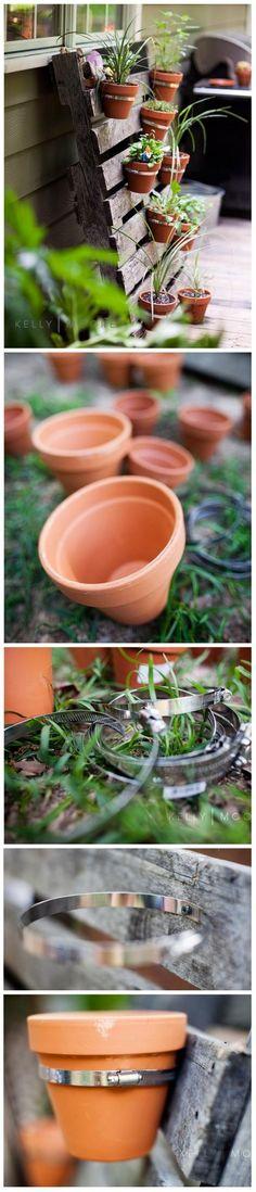 Gebruik een oude pallet om bloempotjes aan op te hangen.