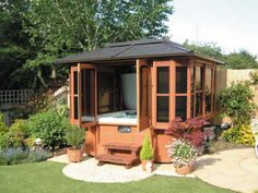 A well landscaped garden featuring a hot tub in a gazebo