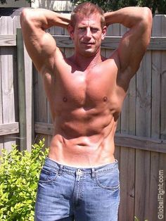 a muscleman jeans flexing outside