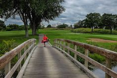 A solitary golfer walks across a bridge enjoying the last good days before winter is upon us again.
