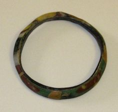 Medieval Islamic Glass Bangle  CULTURE / REGION OF ORIGIN: Islamic, Syria-Palestine.  DATE: 13th – 15th Century CE.  PROVENANCE: Ex collection of a London private gentleman, acquired on  the UK art market in the 1990s. DIMENSIONS:  6.60 cm. (2.6 in.) maximum diameter.