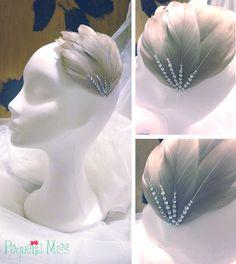 MISS INDARA Tocado confeccionado en base de alta costura sobre la que se han cosido una a una plumas de ánade color visón. Sobre ellas, aplicaciones de strass.